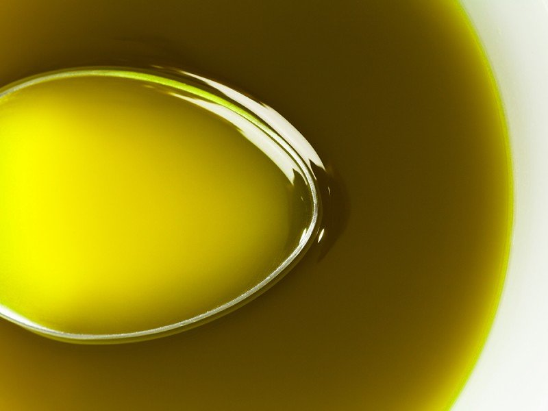 Close up Spoon under extra virgin olive oil.